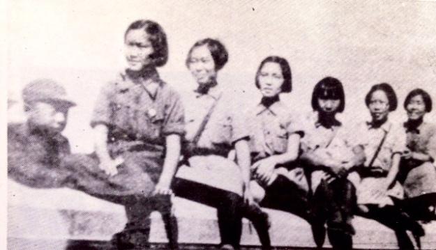 六位年輕的女孩子排成一排,還有她們的隊長一起合影