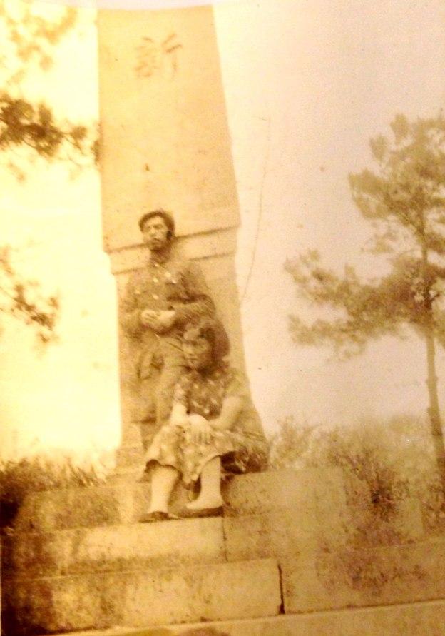 在一塊石碑前,男站立女坐在石階上目視遠方