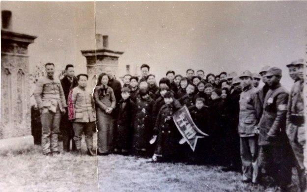 """一群及隧道十幾歲的小孩子,打這一面旗幟:""""孩子劇團""""和大人們合影"""