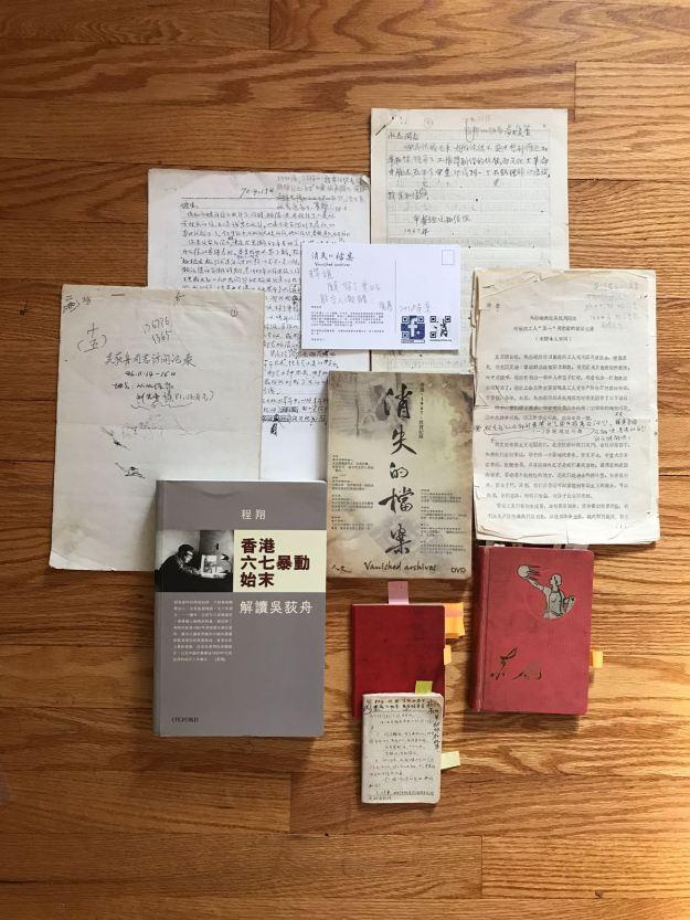 數份孤本文件和筆記本以及紀錄片《消失的檔案》DVD及一本新書合影