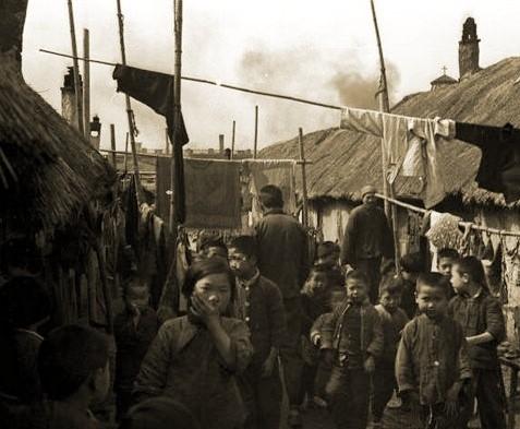 棚戶區環境擁擠,一排排低矮的茅草房,孩子們衣衫襤褸。