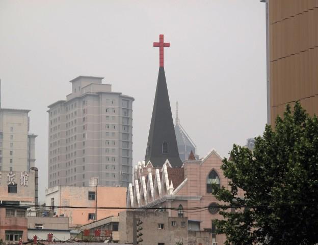 樓群中一個教堂的尖頂,尖頂上有一個紅色十字架