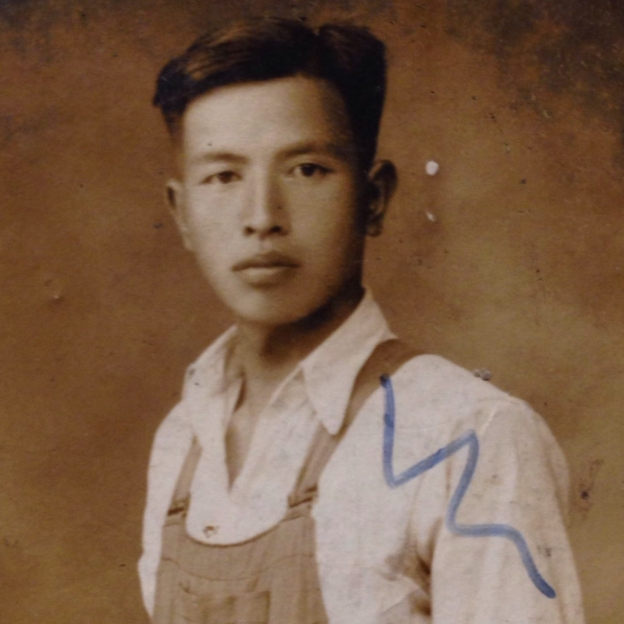 年輕男人,目光堅毅,手插在工裝褲口袋裡沉思