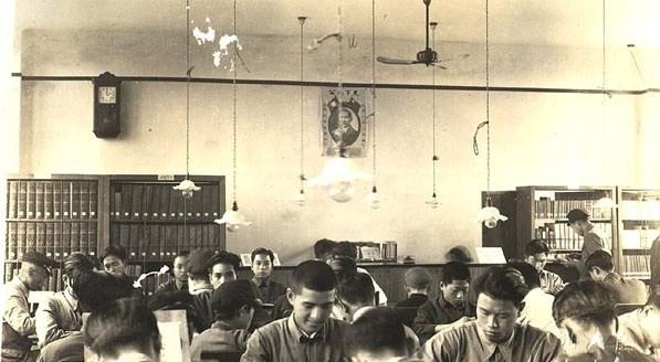 """在寬敞的閱覽室裡,很多男士在讀書。墻上掛著""""天下為公""""的總統畫像。"""