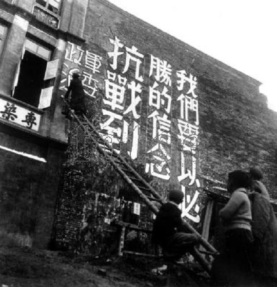 五個年輕人爬梯子在墻上書寫巨型抗戰標語:我們要以必勝的信念抗戰到底!