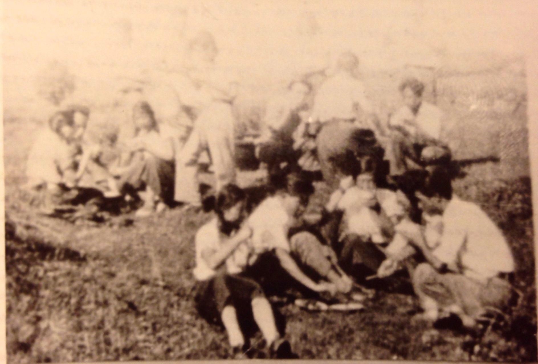 劇宣七隊的隊員在野外席地而坐,幾個人圍在一起,糙米就著一碗青菜就是一頓了。
