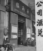 《華商報》三個大字的牌匾掛在一棟普通唐樓門楣上,墻上有閱報欄,門口還有三三兩兩做小生意的人。