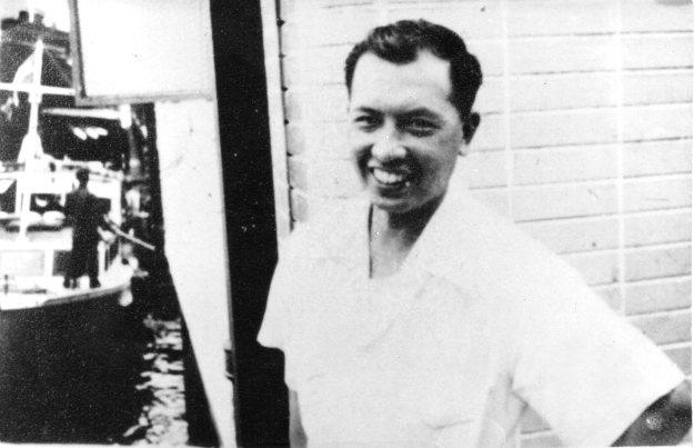 吳荻舟在碼頭附近,身穿白色短袖襯衫,笑容滿面。