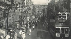 香港島的市井風情,路窄人多,右手邊可以看見路面電車在行人和建築物之間穿行。