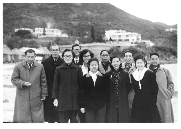 背景為山和一些房屋的一張照片,1954年吳荻舟和黃作梅等11人在赤柱合影。前排左一吳荻舟,後排右一黃作梅。