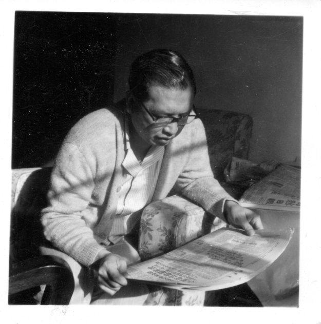 吳荻舟坐在沙發上,藉助窗外照射進來的陽光看報紙。